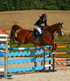 La muchacha que salta en un caballo Fotografía de archivo libre de regalías