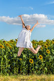 La muchacha que salta en un fondo de un campo de girasoles Foto de archivo