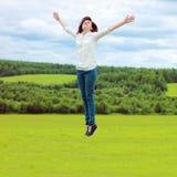 La muchacha que salta en un prado Imágenes de archivo libres de regalías