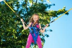 La muchacha que salta en un trampolín Fotos de archivo