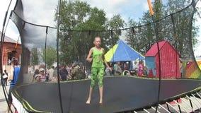 La muchacha que salta en un trampolín en un día de verano soleado almacen de metraje de vídeo