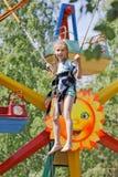 La muchacha que salta en un trampolín del canguro en el parque de atracciones Foto de archivo