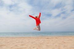 La muchacha que salta en una orilla de mar de la playa arenosa foto de archivo