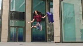 La muchacha que salta para la alegría con el panier a disposición almacen de video