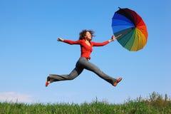 La muchacha que salta sobre hierba con el paraguas colorido Foto de archivo libre de regalías