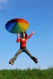 La muchacha que salta sobre hierba verde con el paraguas Imagenes de archivo