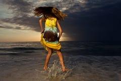 La muchacha que salta y que baila en la playa hermosa. Fotografía de archivo
