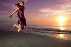 La muchacha que salta y que baila en la playa hermosa. Imagen de archivo