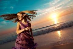 La muchacha que salta y que baila en la playa hermosa. Imagen de archivo libre de regalías