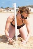 La muchacha que se arrodilla en la arena pone un parasol de playa Foto de archivo