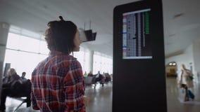 La muchacha que se coloca en el aeropuerto y cuenta con anuncios sobre el aterrizaje en el tablero de los aviones Morenita que co almacen de metraje de vídeo