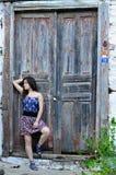 La muchacha que se coloca en pasos cerca de una puerta vieja Imágenes de archivo libres de regalías