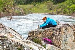 La muchacha que se coloca en rocas acerca al río rápido Fotos de archivo libres de regalías