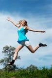 La muchacha que se ejecuta en una hierba contra el cielo Foto de archivo