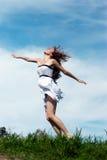 La muchacha que se ejecuta en una hierba contra el cielo Fotografía de archivo