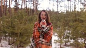 La muchacha que se envuelve para arriba en bebidas de una tela escocesa de un thermomug metrajes