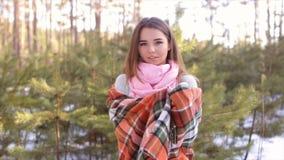 La muchacha que se envuelve para arriba en una tela escocesa en la madera en el invierno metrajes