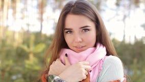La muchacha que se envuelve para arriba en una tela escocesa en la madera en el invierno almacen de video