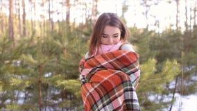 La muchacha que se envuelve para arriba en una tela escocesa en la madera en el invierno almacen de metraje de vídeo