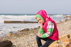 La muchacha que se sentaba en la playa rocosa y el mar perdió feliz en el pensamiento que miraba abajo Imagen de archivo libre de regalías