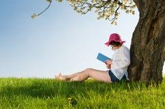 La muchacha que se sienta bajo un árbol del flor lee un libro Foto de archivo libre de regalías