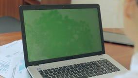 La muchacha que se sienta detrás del ordenador portátil con la pantalla verde almacen de metraje de vídeo