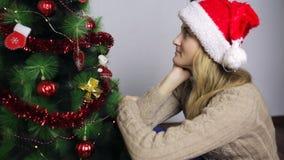 La muchacha que se sienta en el árbol de navidad y piensa almacen de metraje de vídeo