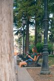La muchacha que se sienta en el banco con el teléfono Fotos de archivo