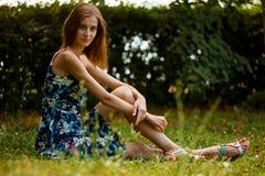 La muchacha que se sienta en el parque con el borde del camino en la muchacha del curbSlender se sienta en hierba verde en un jar Fotos de archivo