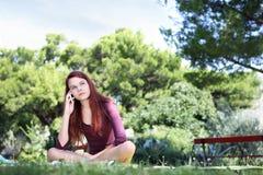 La muchacha que se sienta en el parque con el teléfono celular mira para arriba Imagen de archivo