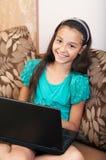 La muchacha que se sienta en el sofá con la computadora portátil Imágenes de archivo libres de regalías