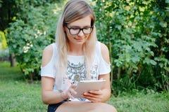 La muchacha que se sienta en la hierba con la tableta en manos Fotografía de archivo
