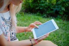 La muchacha que se sienta en la hierba con la tableta en manos Imagen de archivo
