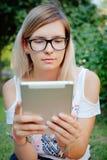 La muchacha que se sienta en la hierba con la tableta en manos Imágenes de archivo libres de regalías