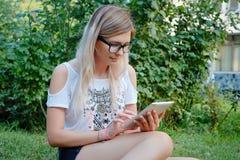 La muchacha que se sienta en la hierba con la tableta en manos Fotos de archivo