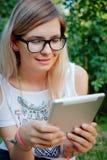 La muchacha que se sienta en la hierba con la tableta en manos Fotos de archivo libres de regalías