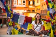 La muchacha que se sienta en la posición de Lotus respecto al stupa budista, rezo señala el vuelo por medio de una bandera Fotos de archivo