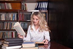 La muchacha que se sienta en los libros de lectura de la biblioteca se está preparando para el examen Foto de archivo