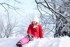 La muchacha que se sienta en nieve en el parque Imagen de archivo libre de regalías