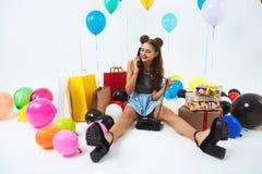 La muchacha que se sienta en piso con el teléfono de casa, recibiendo cumpleaños desea Fotos de archivo libres de regalías