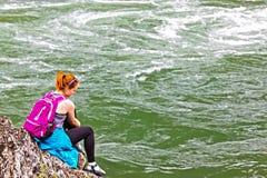 La muchacha que se sienta en rocas acerca al río rápido Foto de archivo libre de regalías