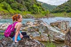 La muchacha que se sienta en rocas acerca al río rápido Foto de archivo