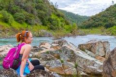 La muchacha que se sienta en rocas acerca al río rápido Imagenes de archivo