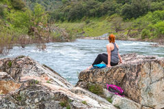 La muchacha que se sienta en rocas acerca al río rápido Fotos de archivo