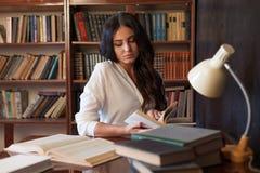 La muchacha que se sienta en la tabla que lee un libro se está preparando para el examen Imagen de archivo libre de regalías