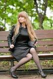 La muchacha que se sienta en un banco Foto de archivo libre de regalías