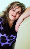 La muchacha que se sienta en un sofá fotos de archivo