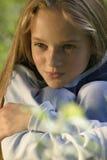 La muchacha que se sienta en una hierba en parque foto de archivo libre de regalías