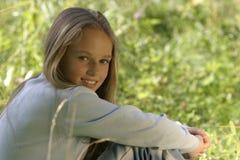La muchacha que se sienta en una hierba en parque Imagenes de archivo