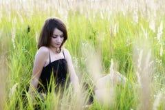 La muchacha que se sienta en una hierba, leyendo un libro Fotografía de archivo